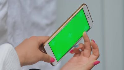 Hand of Woman Uses Smartphone with Green Screen