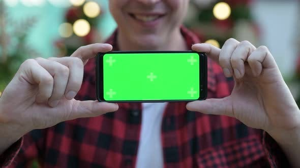 Thumbnail for Hand Of Young Man Showing Phone While Smiling Against Christmas Trees Outdoors