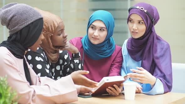Muslim Young Women of Diverse Ethnicity Talking About New Book of Famous Author