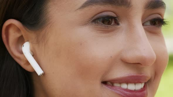 Woman Wearing Earbuds Listening To Music Looking Aside Outdoors Closeup