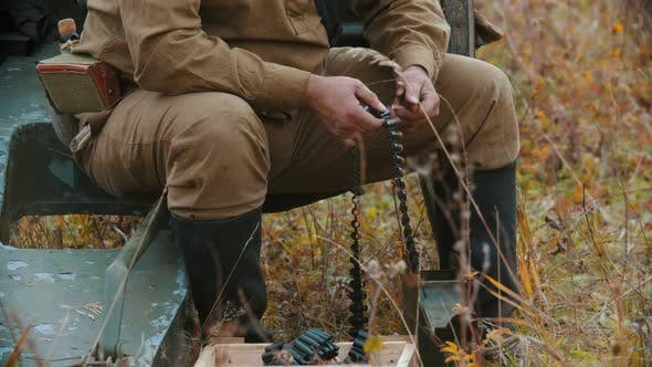 Thumbnail for A Man Soldier Prepares the Ammunition for Charging in the Machine Gun