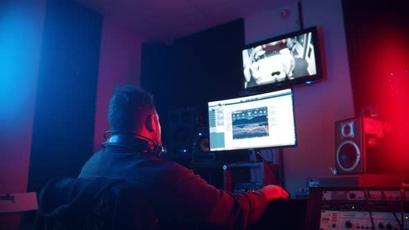 Thumbnail for A Man Sound Engineer in Headphones Editing the Recorded Track of a Man Rapper