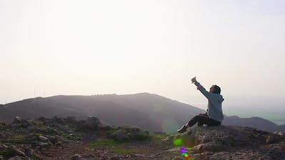 Young Woman Takes Selfie In Scenic Mountains
