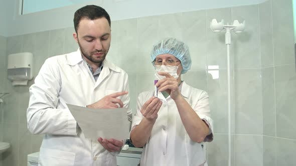 Thumbnail for Male Doctor Talking To Nurse Holding Blood Sample