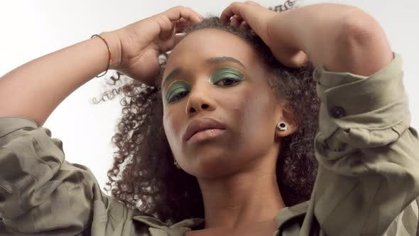 Thumbnail for Young Mixed Race Model in Studio on White with Curly Hair, Bright Green Eye Makeup