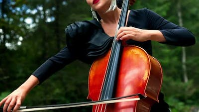 Cello in woman's hands outdoors