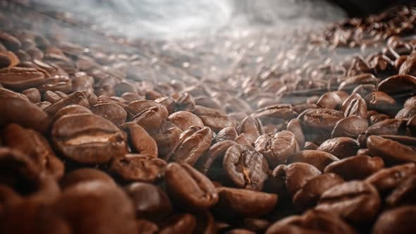 Close Up of Seeds of Coffee. Fragrant Coffee Beans Are Roasted Smoke Comes From Coffee Beans