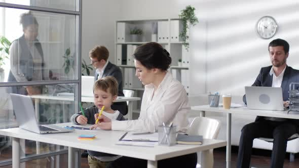 Thumbnail for Businesswoman Working at Desk while Child Drawing with Pencils