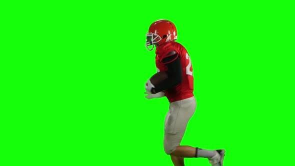 Thumbnail for Fußballspieler Laufen im roten Helm. Grüner Hintergrund. Seitenansicht.