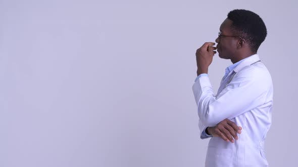 Thumbnail for Profile View of Young Happy African Man Doctor Thinking