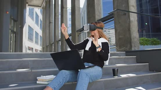 Thumbnail for Woman in Casual Clothes which Sitting on Building's Stairs in Virtual Reality Headset and Working