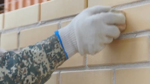 Construction Brickwork. A Close-up of a Hand Builder Seams Between Bricks