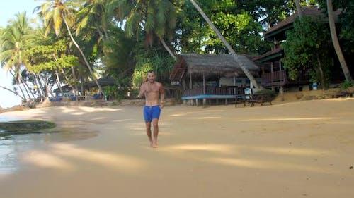 Muscular Man Runs on Yellow Sand Near Wooden Building
