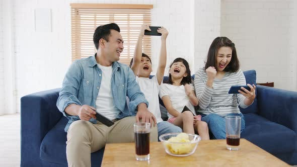 Happy Asian family playing funny game online on smartphone sit sofa in living room at house.