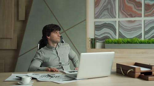 Thoughtful Businessman Sitting on Chair at Office