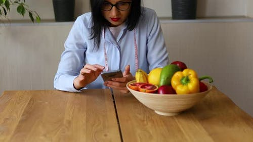 Nutritionist woman with healthy fruit and vegetable using smartphone
