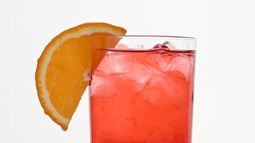 Adding straw to glass of pink cocktail over white