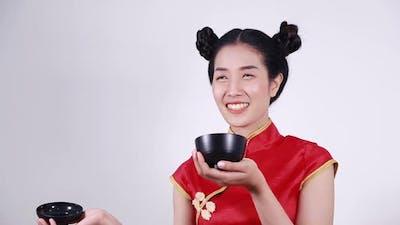 happy woman wearing chinese cheongsam dress with bowl