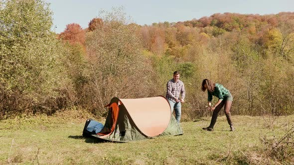 Thumbnail for Beautiful Young Couple Helping Each Other Setting Up the Camping Tent