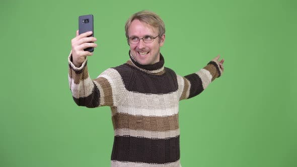 Thumbnail for Studio Shot of Happy Handsome Man Video Calling with Phone