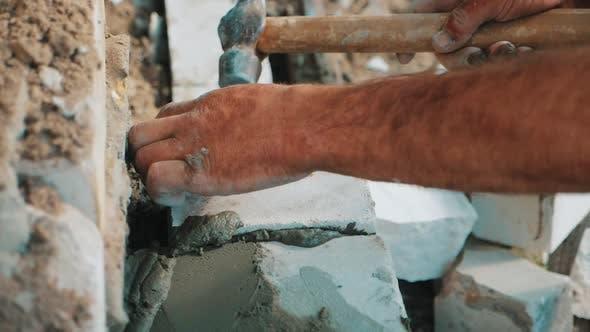 Bauarbeiter oder Maurer, der Ziegelsteine verlegt und Wände schafft. Maurer legen Ziegel zu machen
