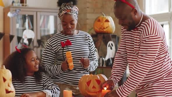 Thumbnail for Joyous Black Family Making Jack-o-Lantern for Halloween