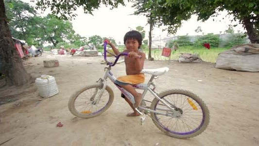 Thumbnail for Cambodian Boy In Slum, Shacks in Background