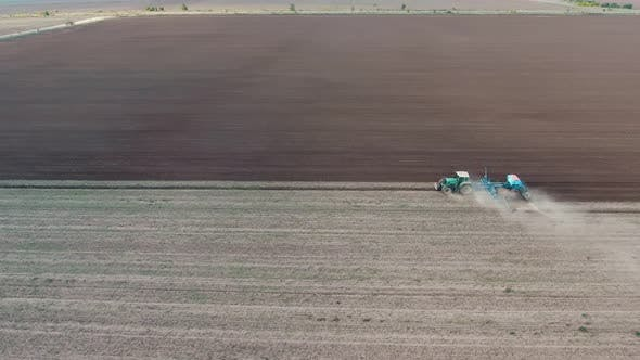 Thumbnail for Aerial Shot of a Wide Agriculture Field with a Tractor Ploughing It in Autumn