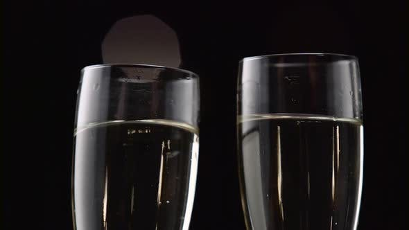 Thumbnail for Two Glasses with Sparkling Champagne Toasting Over Holiday. Bokeh Blinking Black Background. Close