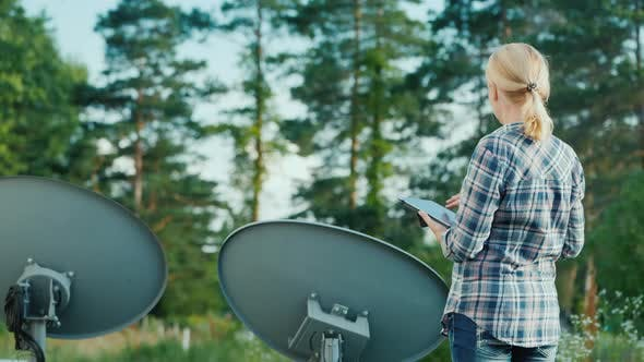 Rear View of Woman Tunes Satellite Dishes Outdoors, Uses Tablet