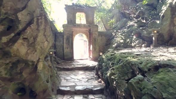 Thumbnail for Bewegung entlang felsiger Mauern zum Steinbogentor in der alten Höhle