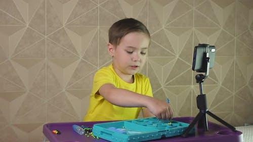 Nettes Vorschulkind kommuniziert per Video anruf mit Familie und Freunden und zeigt, wie es spielt