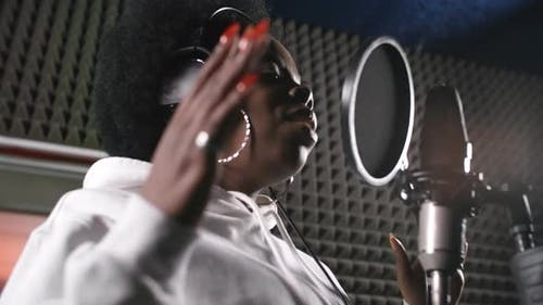 Female Musician Singing Song in Recording Studio