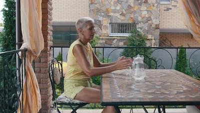 Shorthaired Woman Drinking Water on the Terrace