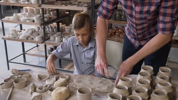Thumbnail for Middle Age Caucasian Father Teaching Little Son How to Work with Clay on Potters Wheel