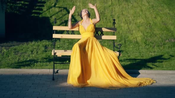 Young Beautiful Girl in a Beautiful Yellow Evening Dress Sitting on a Bench