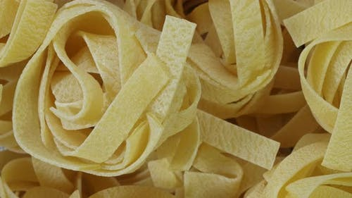 Close Up of Raw Pasta Rotate on Board. Fettuccine, Tagliatelle Pasta. Italian Cuisine. Food