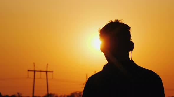 Cover Image for Teenager in Headphones Listening To Music, Looking at a Beautiful Sunset Over the City, View From