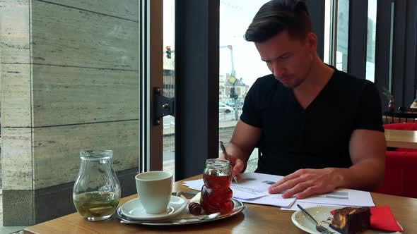 Thumbnail for A Young Handsome Man Sits at a Table with Meal in a Cafe and Does Paperwork