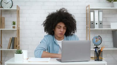Frustrated Student Guy Looking At Laptop Tired Of Learning Indoors