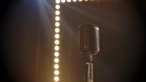 Mikrofon auf der Bühne mit Rauchleucht-Licht dahinter. Professionelles Konzert Vintage Blendmikrofon