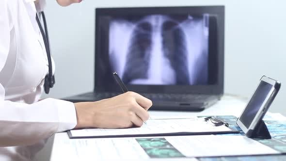 Thumbnail for Doctor Radiologist Makes Notes Using A Laptop