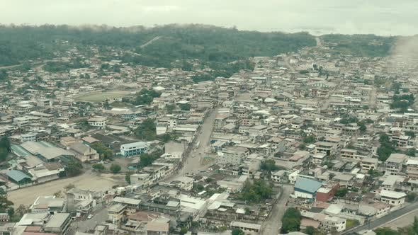 Aerial view going over a large city in South America showing the main street