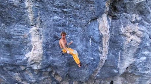 Aerial drone view of a man rock climbing up a mountain and smiling