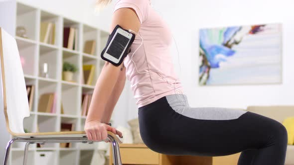 Thumbnail for Woman Listening to Music on Smartphone and Doing Triceps Dips with Chair