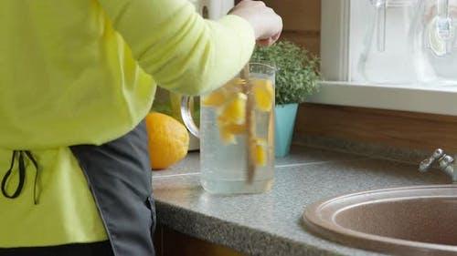 Junge kaukasische Mädchen rührt einen Holzlöffel mit Zitrus-Lemonade in der Küche