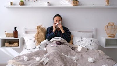 Woman with Flu Talking on Phone in Bed at Home