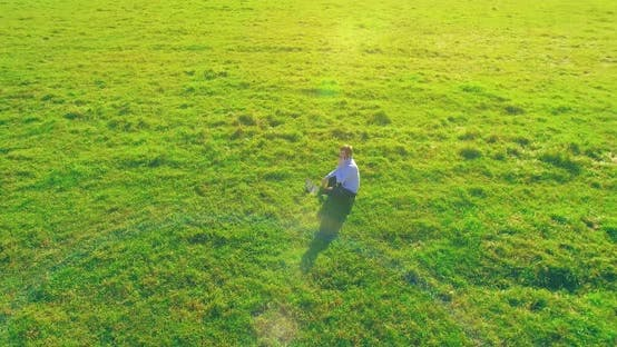 Cover Image for Low Orbital Flight Around Man on Green Grass with Notebook Pad at Yellow Rural Field