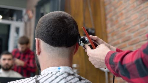 Young Stylish Hairdresser in a Plaid Red and Black Shirt Makes a Haircut on the Back of the Client's