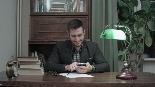Cover Image for Young Writer at His Desk Happily Messaging on Mobile Phone